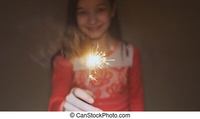 Teen girl posing and laughing with burning sparklers