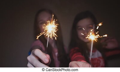 Two teen girls posing and laughing with burning sparklers.