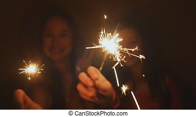 Two teenage girls posing and laughing with burning...