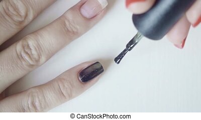 Application of colored nail of lacquer on the right hand...
