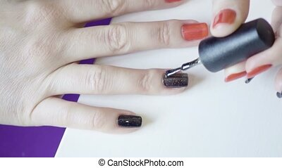 Application of colored nail of lacquer on the right hand in...