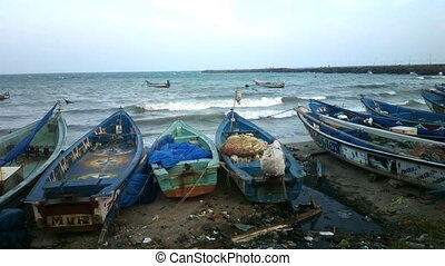 Beach of Indian ocean. Fishing boats waiting out at sea