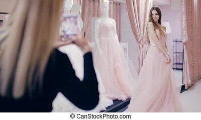 Pretty girl trying on prom gown in fitting room - girl...