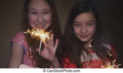 Two teen girls posing and smiling lit sparklers