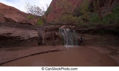 Hiker cooling off near Waterfall on a lower section of the...