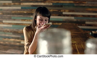 Beautiful woman at cafe making voice message with cell phone...