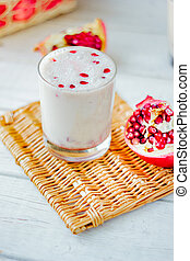 Indian dessert - lassi with pomegranate on brown board.