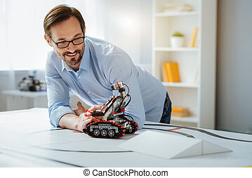 Possitive professional engineer testing robot in a lab -...