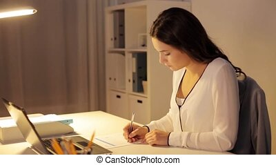 woman with laptop and papers at night office - business,...