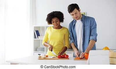 happy couple with tablet pc cooking food at home