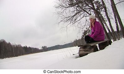 Young blonde woman in pink coat sitting at bench in winter forest