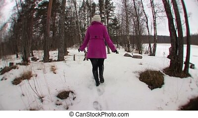 Young blonde woman in pink coat running in winter forest