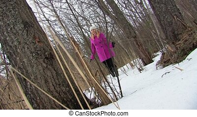 Young blonde woman in pink coat walking in winter forest