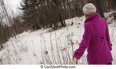 Young woman in pink coat walking in winter forest and touching branches