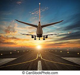 Airplane landing to airport runway in sunset light -...
