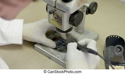 Scientist in the lab looking into a microscope and solder,...