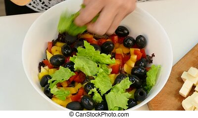 Female hands in bowl with chopped vegetables adds cheese cut...