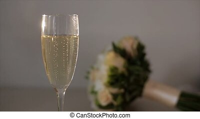 Wedding rings falls to glass of champagne, bouquet on...