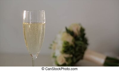 Glass of champagne, bouquet on background