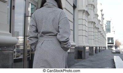 Female walking along city street - Back view of brunette...