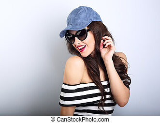 Happy enjoyment young woman in sun glasses and blue cap posing and looking down posing in striped clothing. Closeup portrait