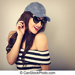 Happy enjoyment young woman in sun glasses and blue cap posing and looking down posing in striped clothing. Closeup toned vintage portrait