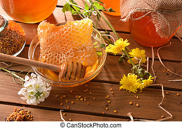 Honey pots with honeycomb on wood table top elevated view -...
