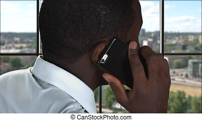 Phone talking on city backdrop. Afro-american guy with...