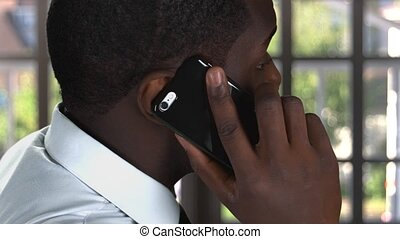 Phone talk of black man. Guy with cellphone indoors. Whom to...