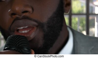 Black man singing. Guy with microphone closeup. Singer in...