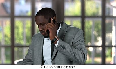 Black businessman phone talking. Man in a suit smiling. How...