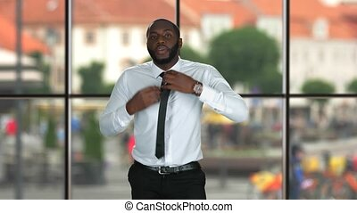 Guy fixing tie. Formally dressed black man. Business fashion...