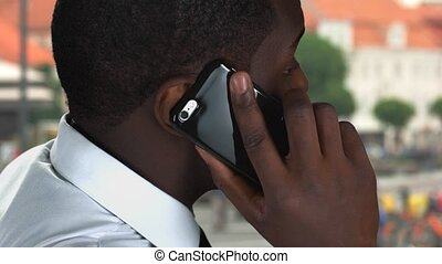 Phone talking on street background. Black male holding...