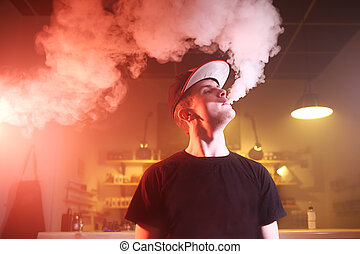 Vaping man in a cloud of vapor in a vape bar - Vape. Vaping...