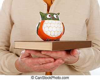 Book & owl symbol of wisdom - Close up picture of an elderly...