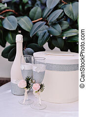 Two decorated newlyweds glasses and bottle of champagne on...