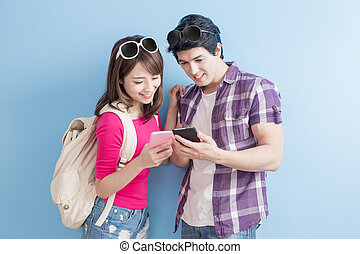 young couple use phone happily with blue background