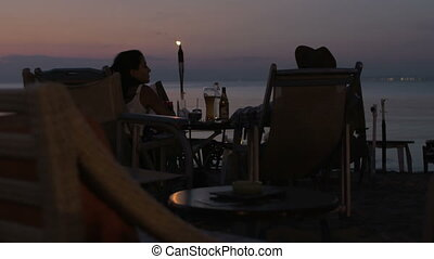 Couple spending evening in cafe on the beach - Man and woman...