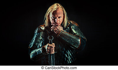 Powerful blond knight with the sword on the dark background