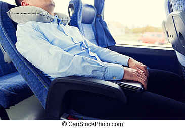 close up of man sleeping in travel bus with pillow -...