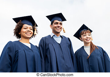 happy students or bachelors in mortarboards