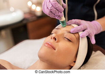 woman having microdermabrasion facial treatment - people,...