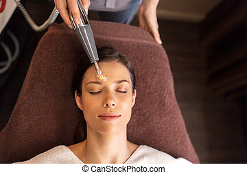 woman with microcurrent face massager in spa - people,...