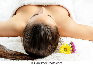 Woman laying on massage bed in spa. - Close up of young...