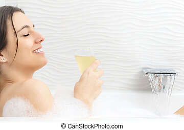 Relaxed young woman with champagne in foam bath. - Close up...