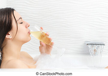 Young woman relaxing with champagne in foam bath. - Close up...