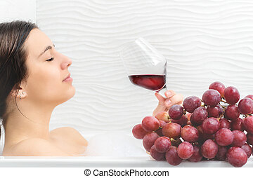 Young woman relaxing in foam bath with red wine. - Close up...