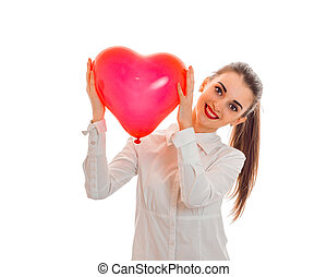 cute young girl in shirt smiling and holding a large heart-shaped balloon