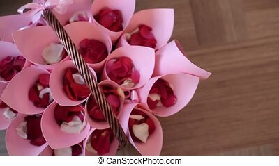 Red rose petals in pink bags at basket