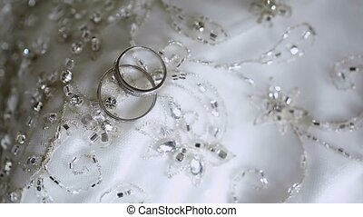Wedding rings on white lace background with rhinestones